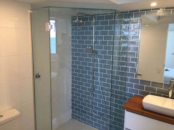 enclosured shower with blue subway feature tile