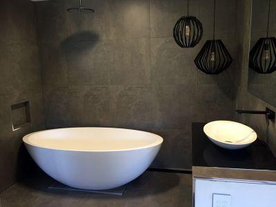 Egg shaped free-standing bath, with feature lighting and dark tiles.