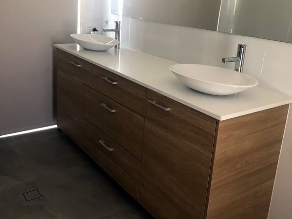 Wooden vanity with white stone top and double porcelain sinks.